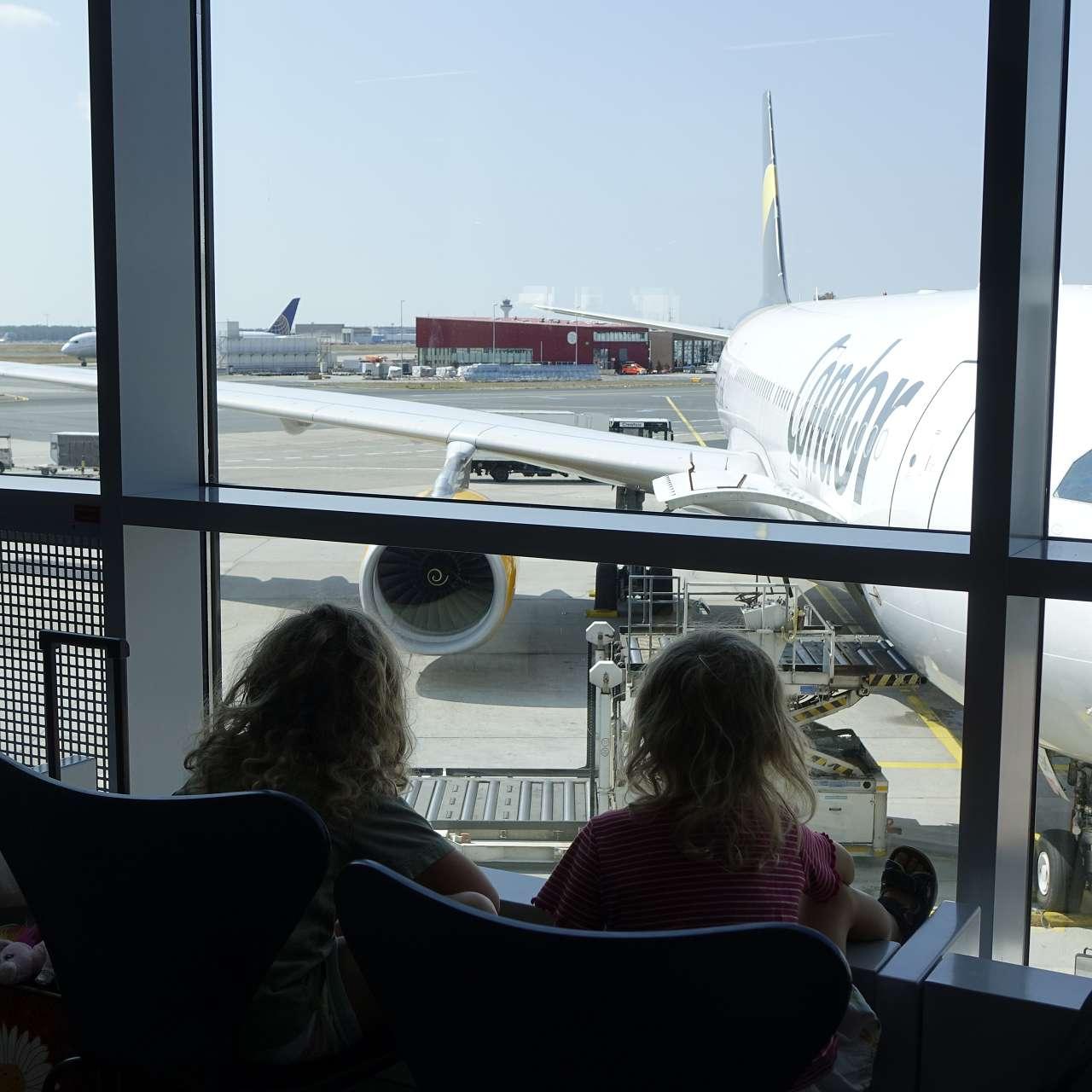 2 Mädchen beobachten den Flufverkehr auf der Start- und Landebahn
