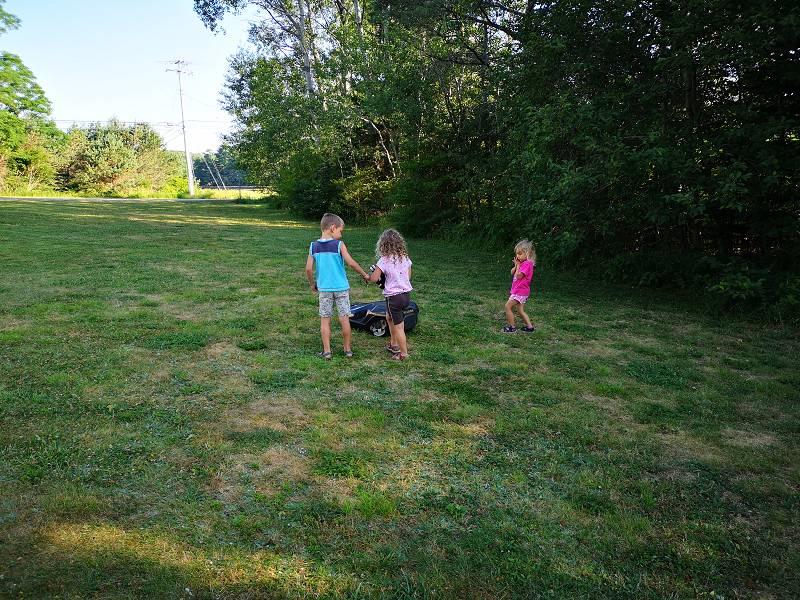drei Kinder laufen neben einem Mähroboter im Gras