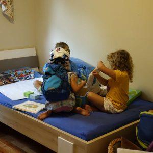 drei Kinder spielen auf dem Bett