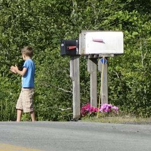 ein Junge hat in die Mail Box geschaut und läuft wieder zum Haus