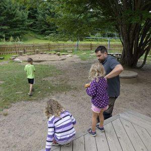 Mann und drei Kinder gehen in den Garten der South Shore Waldorfschule
