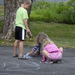 drei Kinder malen mit Straßenmalkreiden