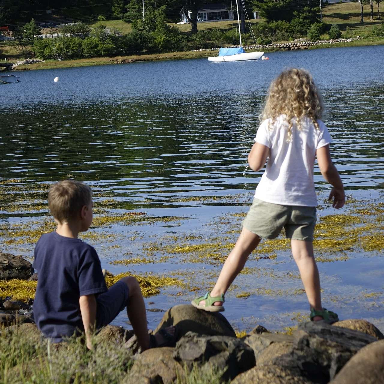 2 Kinder spielen und werfen Steine in den Atlantik