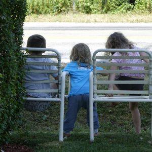 drei Kinder an der Straße warten auf vorbeifahrende Autos