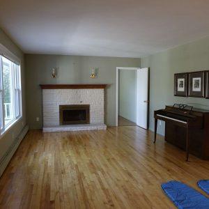 großes Wohnzimmer mit Klavier und Ofen