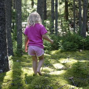 kleines Mädchen läuft durchs Moos im Wald