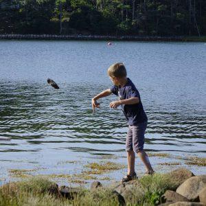 ein Junge wirft einen Stein ins Meer
