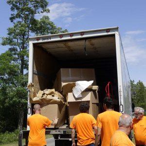 5 Männer räumen Kartonreste in den LKW