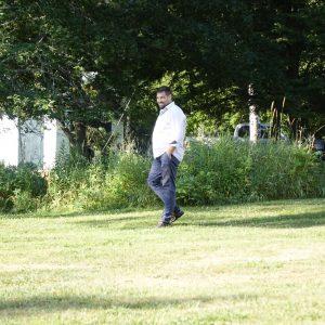 ein lächelnder Mann läuft glücklich durch seinen Garten