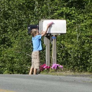 der Junge macht das Fähnchen an der Mail Box runter