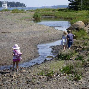 drei Kinder laufen am Wasser entlang