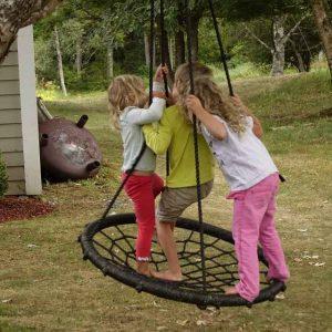 3 Kinder stehen in der Affenschaukel