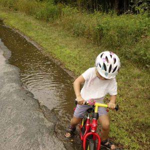 Kind fuhr mit Laufrad durch die lange Pfütze