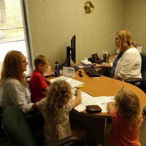 Frau mit 3 kindern sitzt beim Banktermin