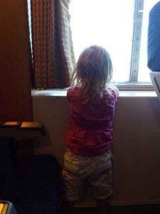 Mädchen steht am Fenster der Fähre und schaut hinaus