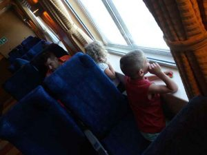 Mann und zwei Kinder sind in Sitzen auf der Fähre. Kinder schauen aus dem Fenster