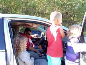 mann und drei Kinder sind im Auto und beobachten etwas vor sich