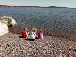 drei Kinder sitzen am Strand und schauen aufs Meer