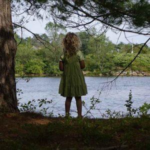 Mädchen in grünem Kleid schaut aufs Wasser