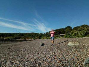 Mann fotografiert am Strand mit blauem Himmel vor dem Wald
