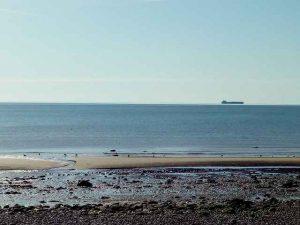 Stein und Sandstrand mit großem Schiff weit draußen auf dem Meer