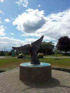 Statue Walflosse an Rastplatz mit blauem Himmel im Hintergrund